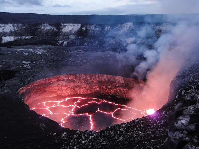 """A view of the summit lava lake at dusk on Feb 1, 2014. The lava lake is contained within a crater informally called the """"Overlook"""" crater (due to its position immediately below the former Halemaʻumaʻu visitor overlook), and this crater is set within the larger Halemaʻumaʻu Crater. The photo was taken from the rim of Halemaʻumaʻu Crater. The lava lake is about 50 m (160 ft) below the rim of the Overlook crater. The level has dropped slightly the previous day, leaving a black veneer of lava on the crater walls just above the current margin and easily visible in this photograph."""